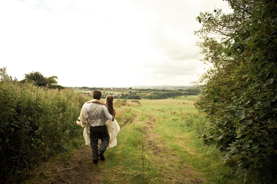 groom carries bride down to pretty field