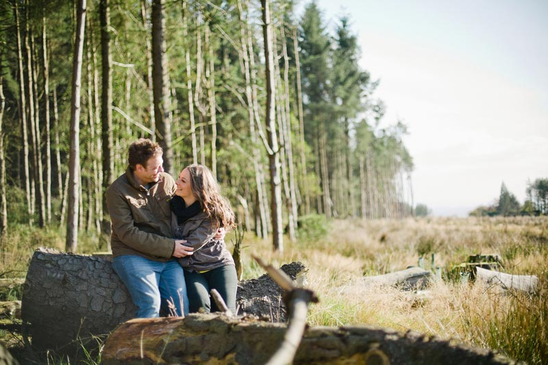 Photograph of the bride and groom sat on a log.