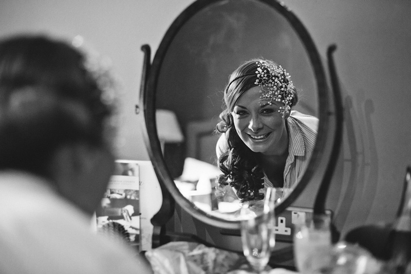 Beautiful bride looking into mirror at Egerton House Hotel in Bolton