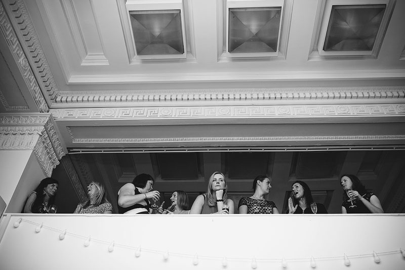Black and white picture of some girls chatting with one in the middle looking bored