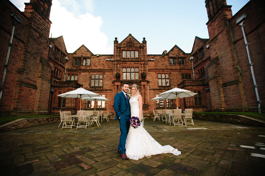 lisa and christian stand in front of their huge wedding venue