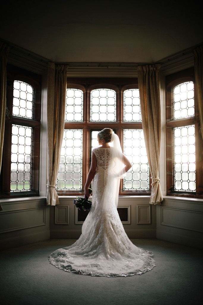 lisa poses in her dress in front of a large bay window