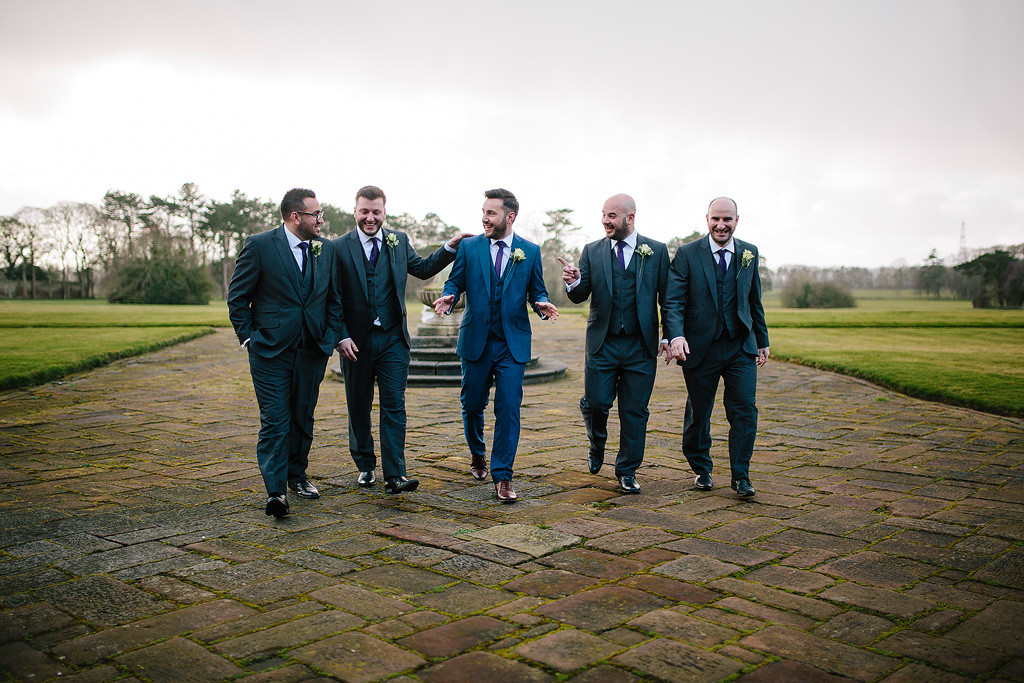 the groomsmen walking to wards the wedding venue