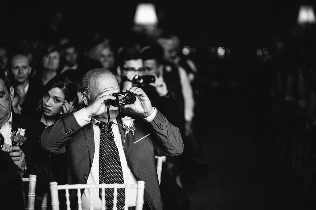 a relative takes a photo of the couple