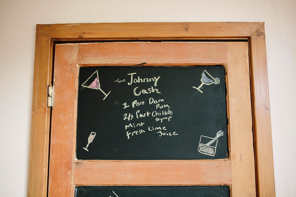 a list of cocktails on the door to the living room in their house