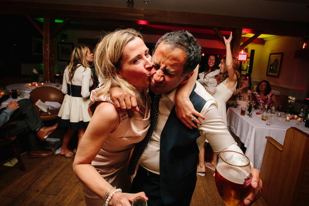the groom gets a kiss from a random guest