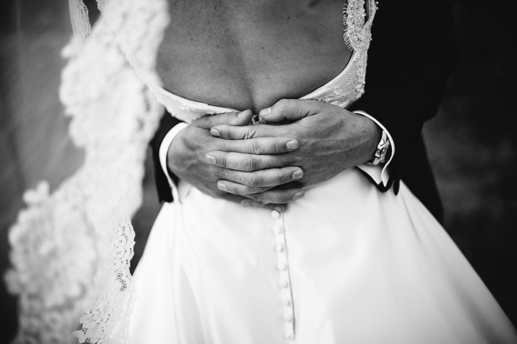 a beautiful black and white photo of a mans hands around his wife's waist
