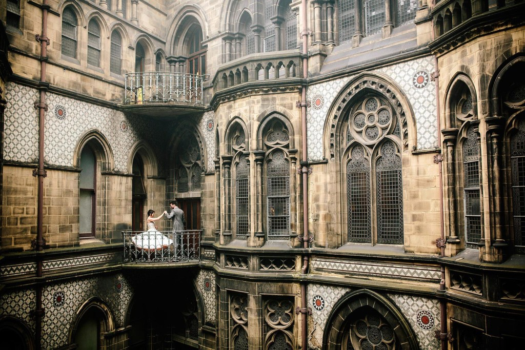 the groom and his wife dance on the balcony of manchester town hall
