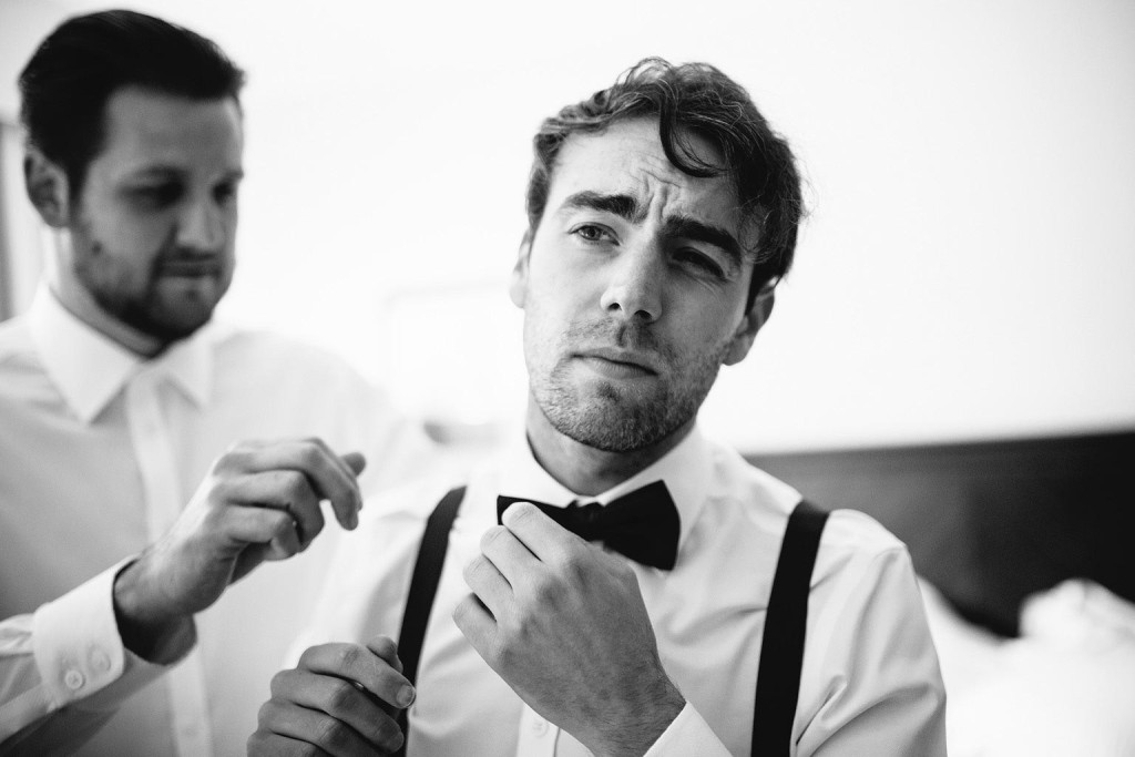 a bow tie is tied by a groomsman