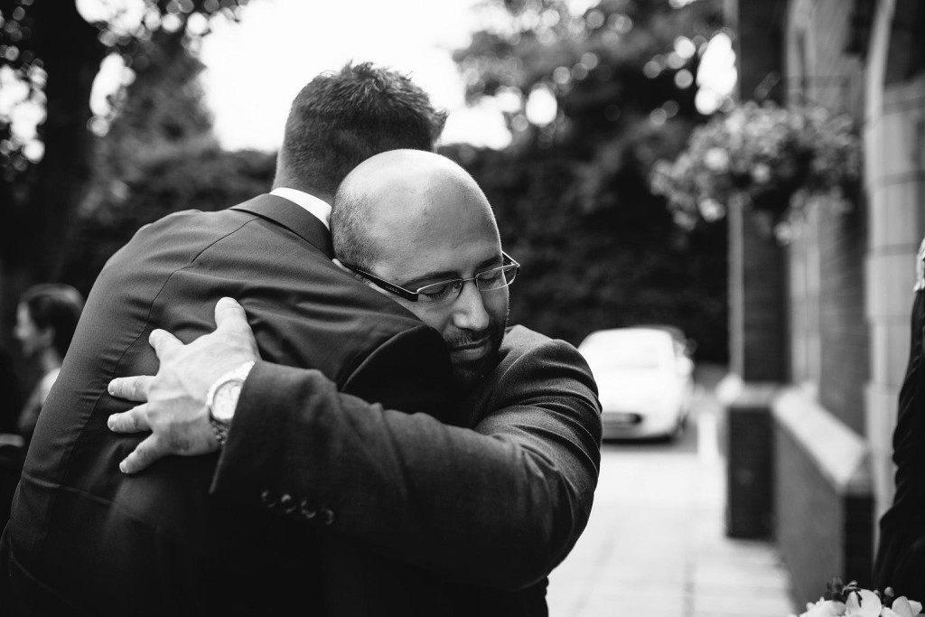 amazing photo of the groom hugging his friend