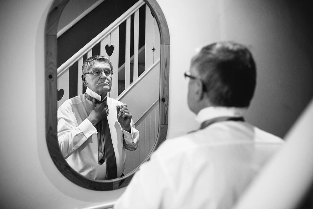 kate's dad ties his tie in the mirror