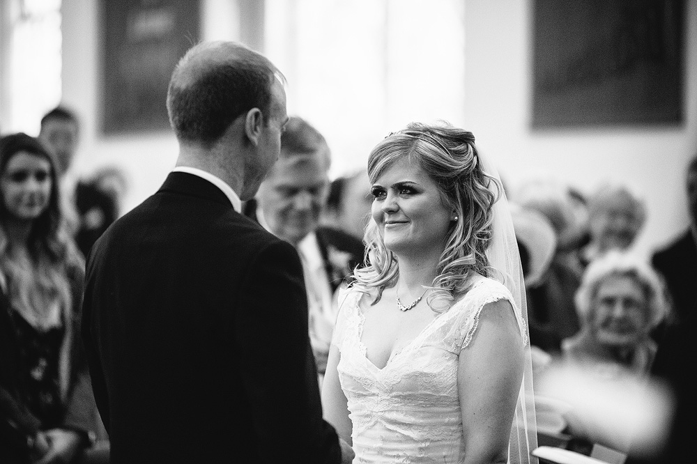 a balck and white photo of kate looking at simon as he says his wedding vows