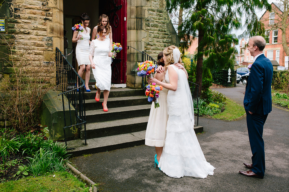 the bride is hugged by a bridesmaid