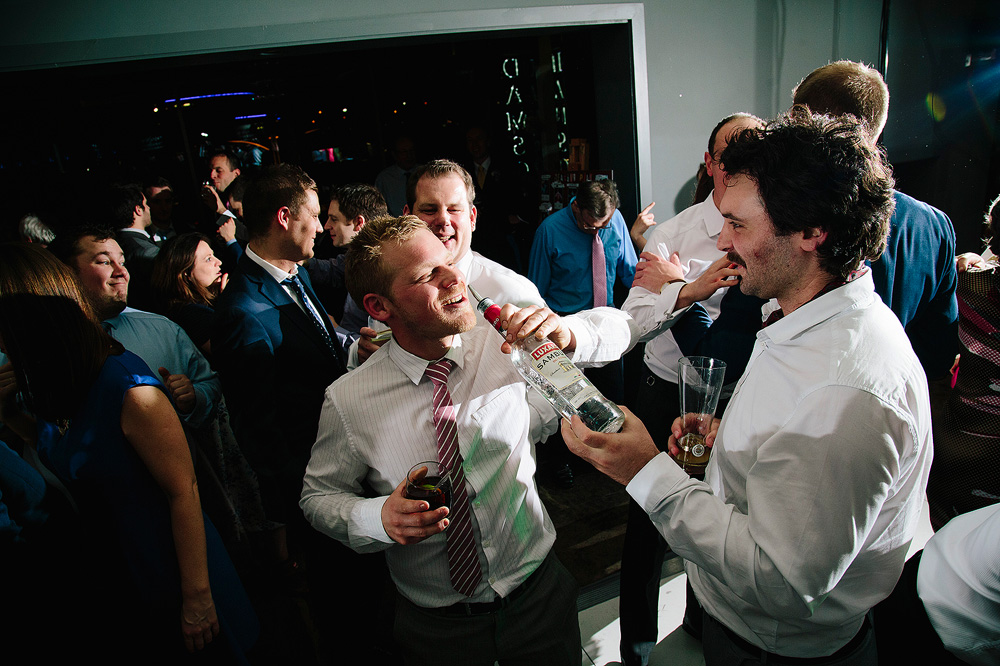 two lads lark about on the dance floor with a bottle of vodka
