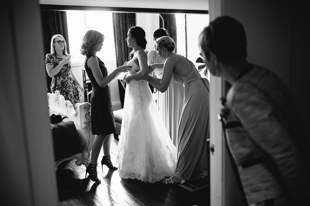 the bride's mother looks on as the girls get shelley into her dress