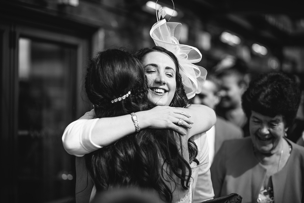 The bride is hugged by one of her friends.
