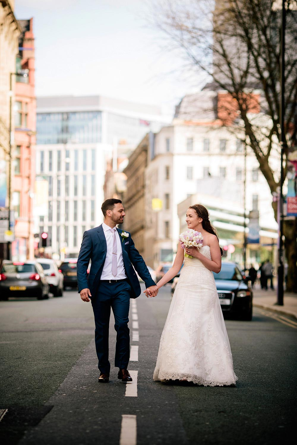 The bride and groom walk down Quay Street in Manchester city centre.
