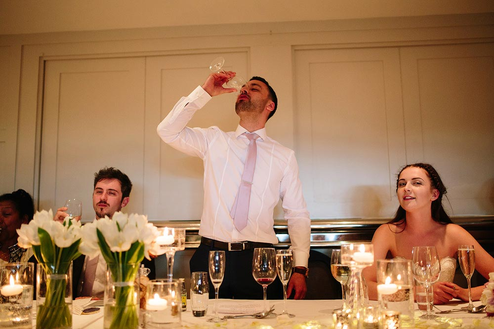 The groom drinks a shot of a very alcoholic drink.