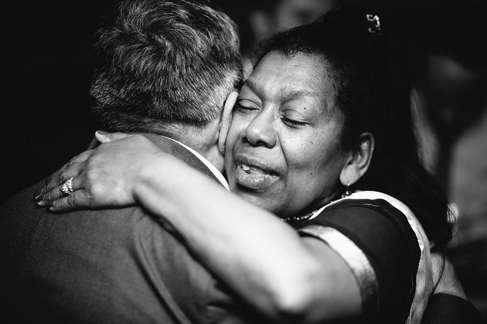 The groom's mum hugs her husband.