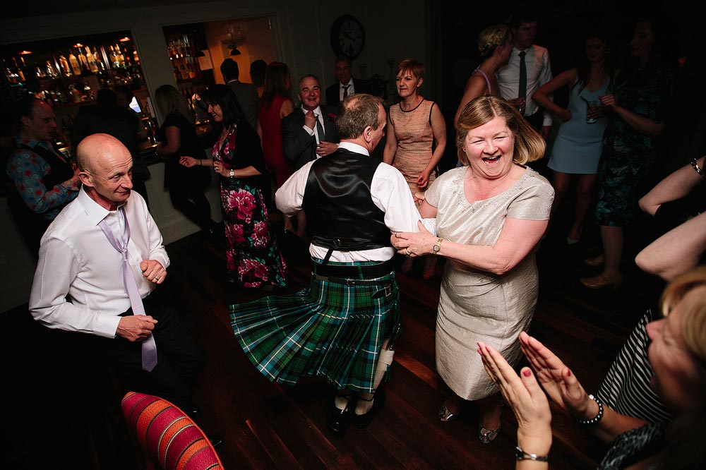 A man in a kilt spins his wife around on the dance floor.