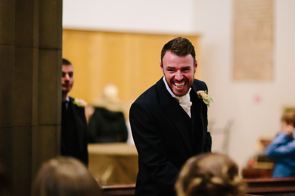 The groom smiles at a guest.