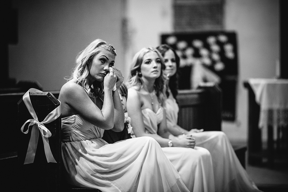 One of the bridesmaids wipes a tear from her eye.