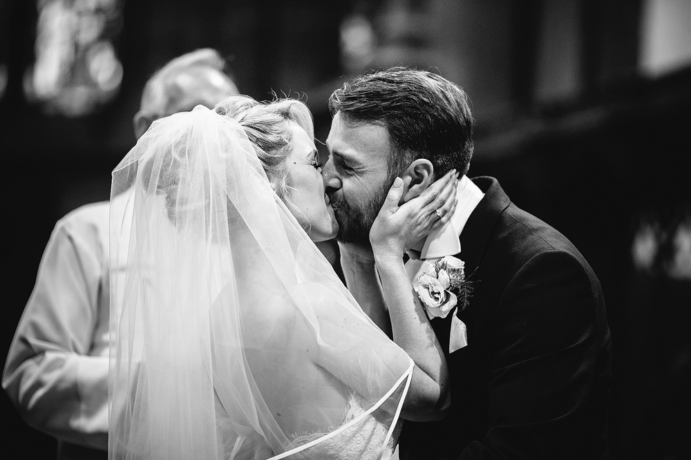 The bride and groom share their first kiss.
