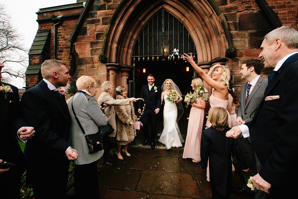 The bride and groom walk out of the church to a storm of confetti.