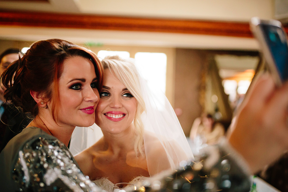 The bride takes a selfie photograph with a guest.