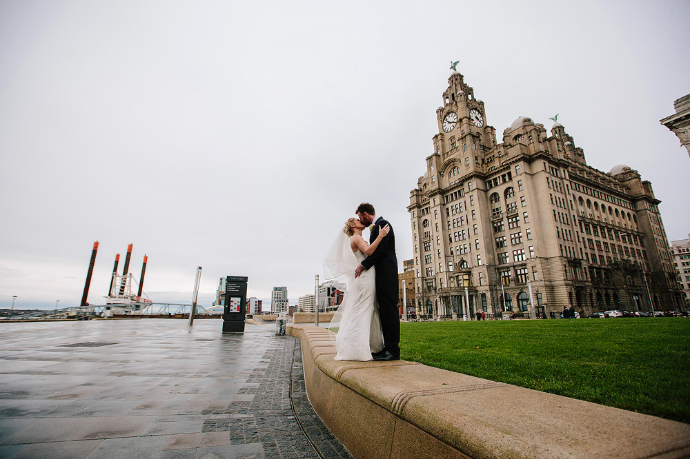 The couple stand in front of the Liver Buildings.
