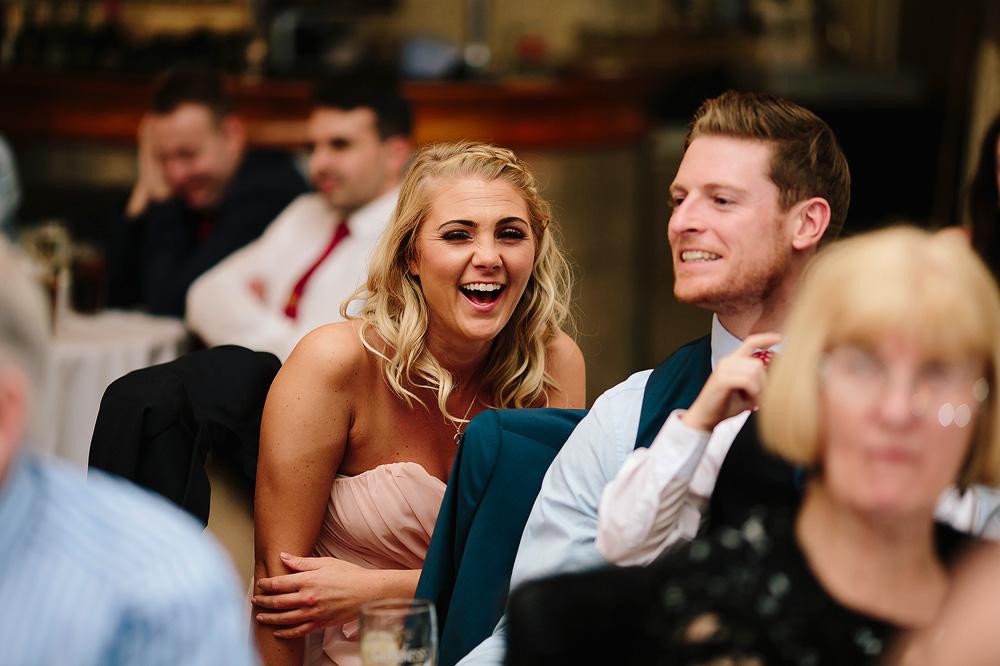 A bridesmaid enjoys the speech.