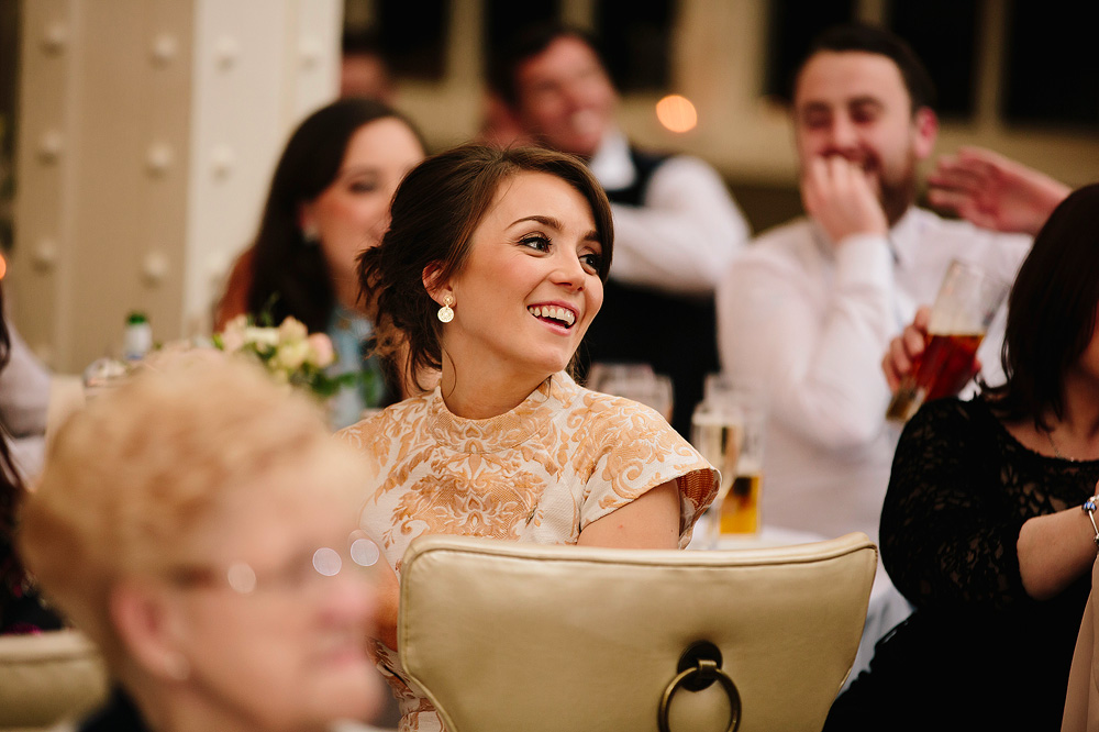 A guest laughs along with the best man.