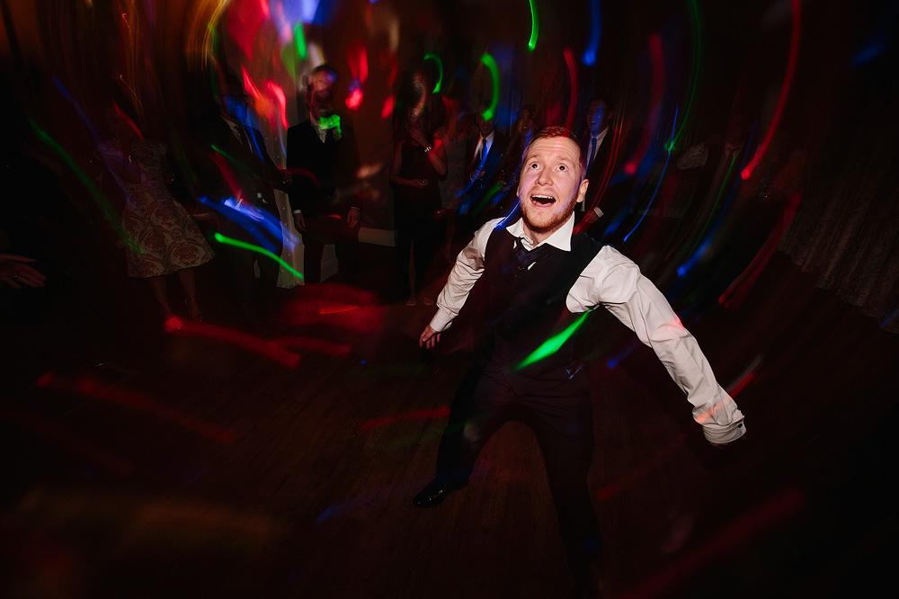 A groomsman dances in the night.