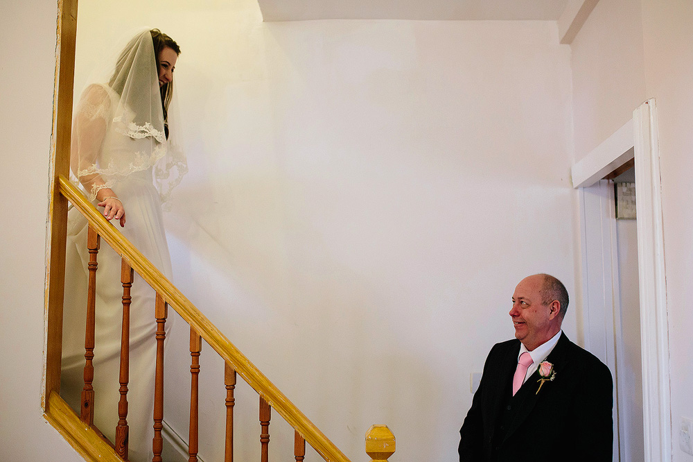 The father of the bride waits at the bottom of the stairs.