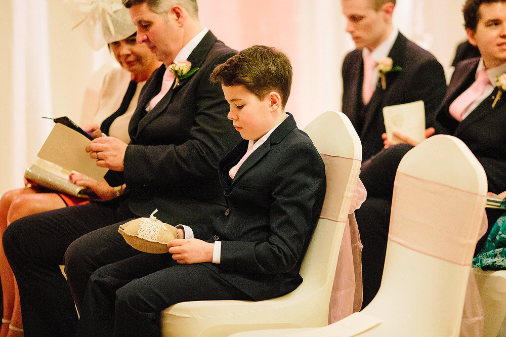 The page boy holds the wedding rings.