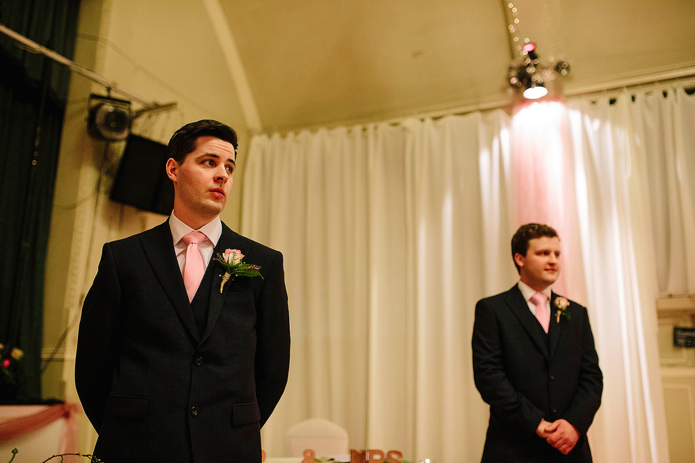 Tom looks to see his bride enter the room.