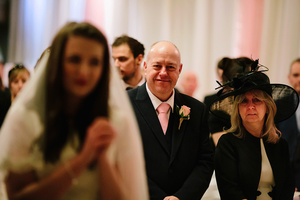 The father of the bride smiles at the happy couple.