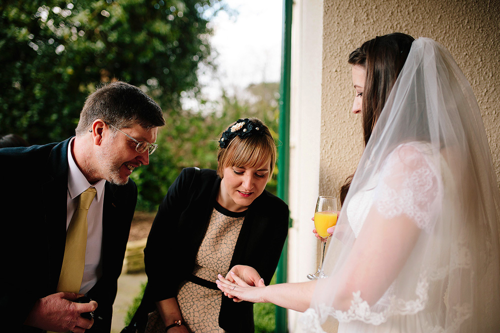 The bride shows her ring to some guests.