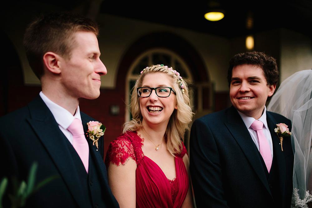 A bridesmaid laughs at an usher.