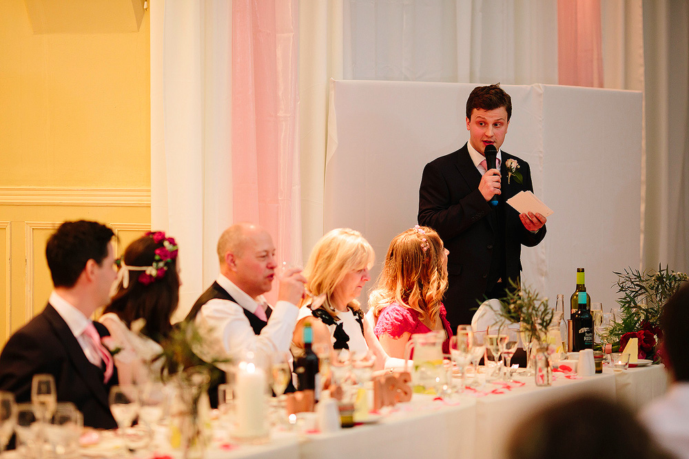He tells some jokes about the groom.