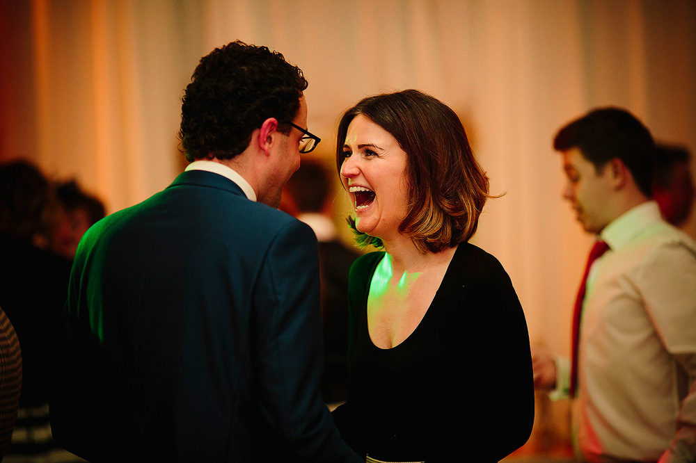 A woman laughs at her husband.