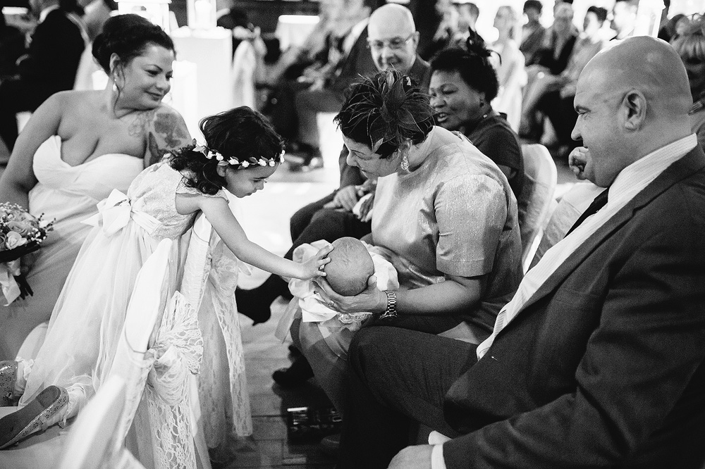 The flower girl touches her baby sister on the head carefully.