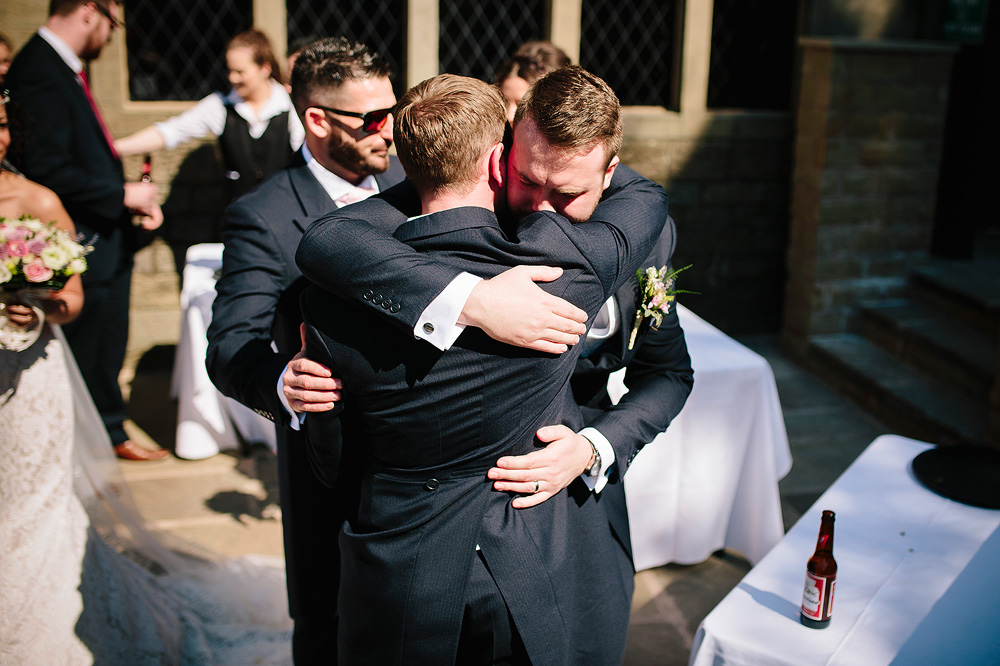 The groom hugs the best man.