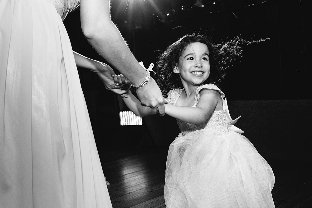 The flower girl spins on the dance floor.