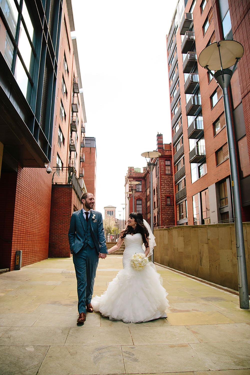 natural wedding photography as the couple walk down the alley
