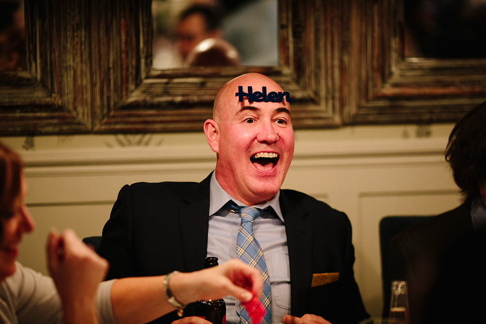 one of the guests sticks his wedding place name on his head