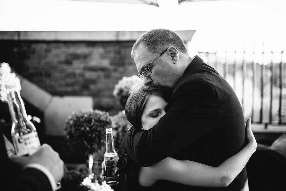 one of the bridesmaids is hugged by her grandad