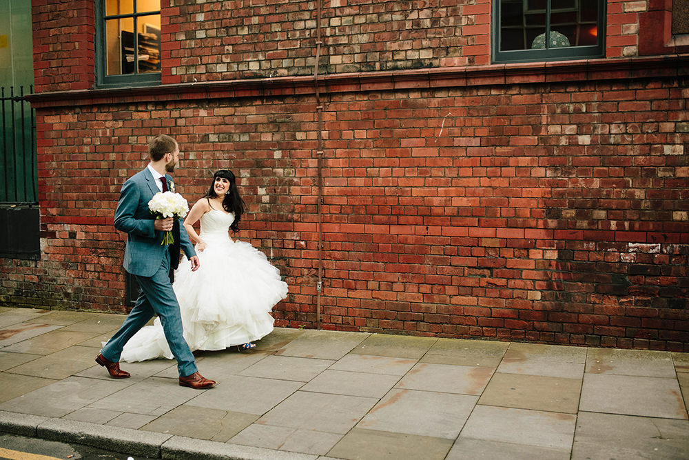 the bride and groom walk aling the pavement laughing