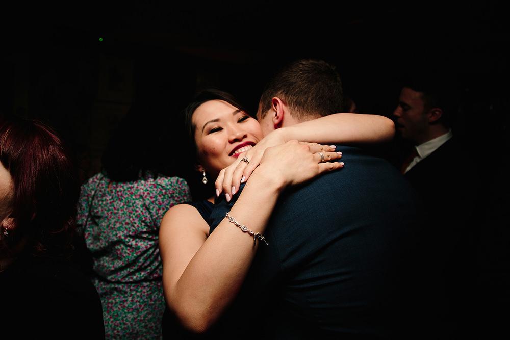 a bridesmaid hugs her partner