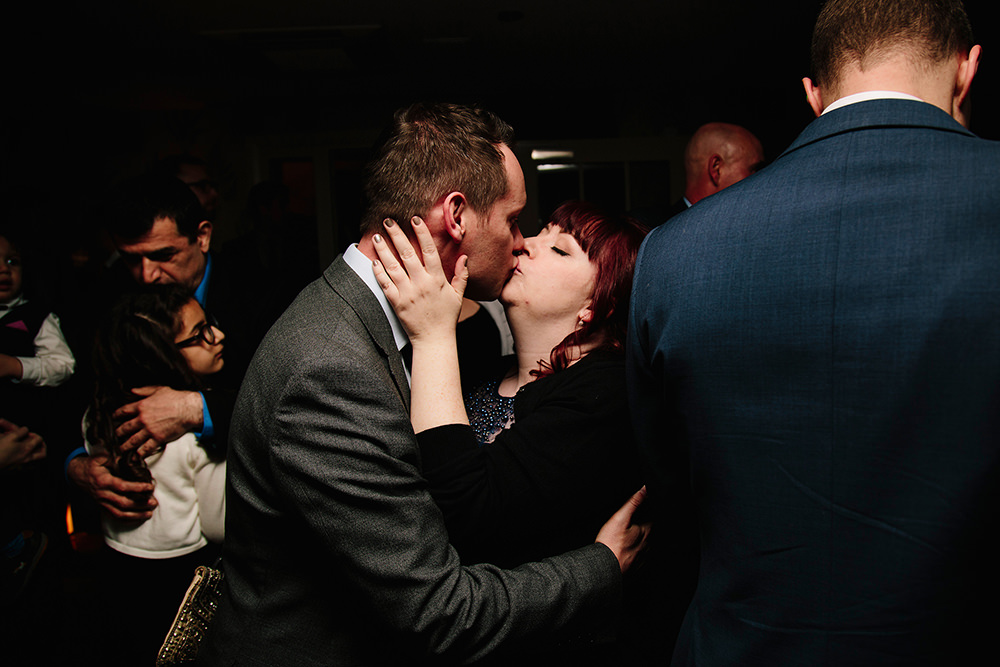one of the bridesmaids kisses her husband